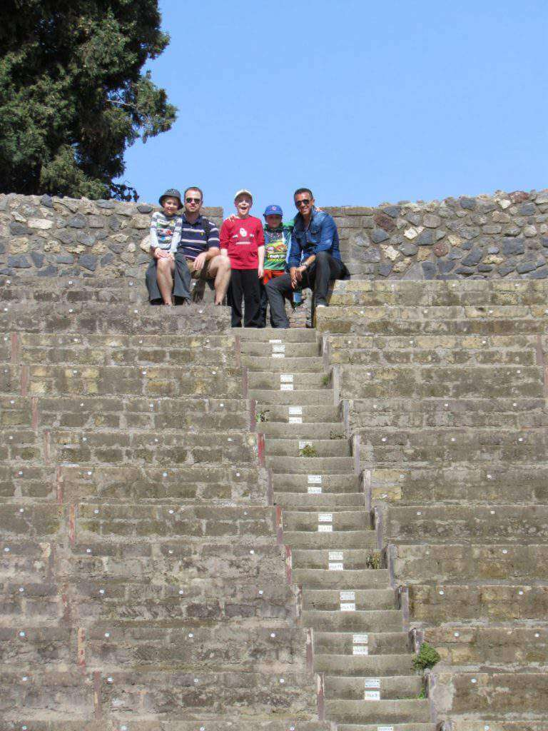 How to Visit Sorrento, Capri, and Pompeii with Kids taking a break in the amphitheater- Kids Are A Trip